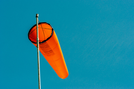 Downward angled plain orange windsock against a clear blue sky.