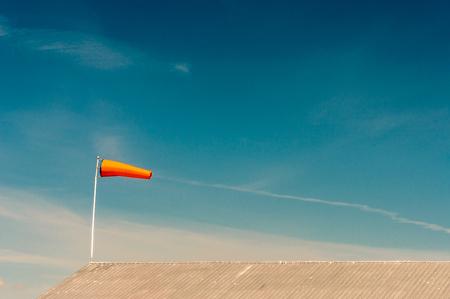 Horizontally flying orange windsock on metal rooftop and clear dark blue sky.