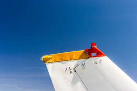 Tail fin, rudder and beacon lights, small single engine airplane with old paint and bright blue sky. Stock fotó