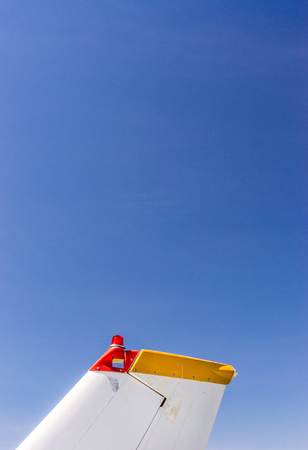 Tail fin, rudder and beacon lights, small single engine airplane with old paint and bright blue sky. Reklamní fotografie