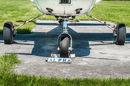 Small single engine airplane wheels and landing gear on parking pad with wheel chocks.