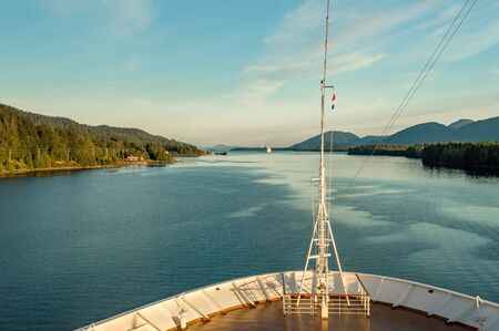 Pointed bow of cruise ship , southbound on ocean channel, Alaska Inside Passage, in warm afternoon sun.
