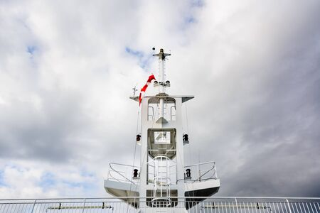 Ship navigation tower mast with Canadian flag and cloudy sky.