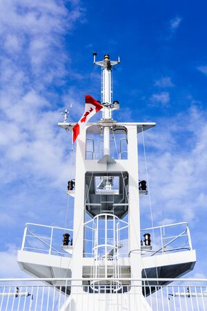 White ship communication tower mast, rear view from below with Canadian flag against cloudy blue sky.