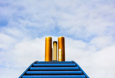 Simple graphic front view of ship exhaust pipes and blue cowling against blue sky with clouds.