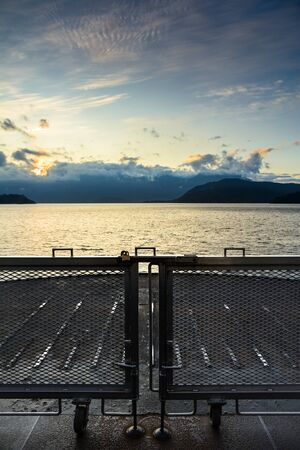 Sunrise over ocean and mountains from front of ferry car deck, Howe Sound near Gibsons, Canada.