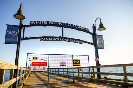 White Rock, Canada - March 25, 2020: Pier closed to general public during time of Covid-19 pandemic. Notification signs are affixed to fence blocking access to the popular pier.