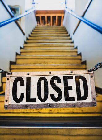 Metal closed sign on chain hanging across stairyway during Coronavirus pandemic