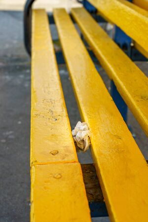 Pair of used nitrile medical gloves discarded in between slats on public seating during Coronavirus Covid-19 pandemic Stok Fotoğraf