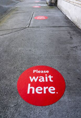 Red physical distancing sign on sidewalk during Coronavirus Covid-19 pandemic