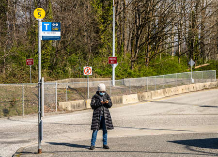 N. Vancouver - Apr 7, 2020: Woman weaing surgical mask, using smartphone, waiting at bus stop during Covid-19 pandemic