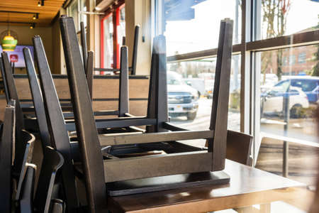 N. Vancouver - Apr 7, 2020: Restaurant chairs stored on top of tables at closed Tim Hortons coffee shop during Covid-19 pandemic