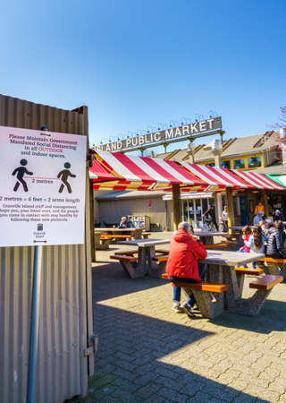 Vancouver, Canada - Apr 7, 2020: Public seated outdoors at Granville Island Market courtyard during Coronavirus pandemic