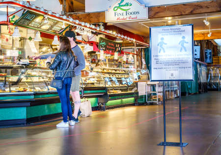 Vancouver, Canada - Apr 7, 2020: Couple buying take-out food inside Granville Island Market during Coronavirus pandemic Editöryel