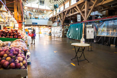 Vancouver, Canada - Apr 7, 2020: Produce shopper in empty Granville Island Market artisan space during Covid-19 pandemic
