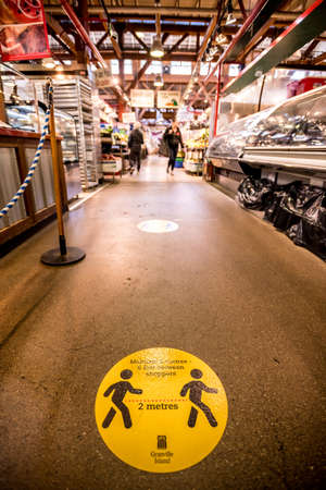 Vancouver, Canada - Apr 7, 2020: Social distancing sign on floor of Granville Island Market during Coronavirus pandemic