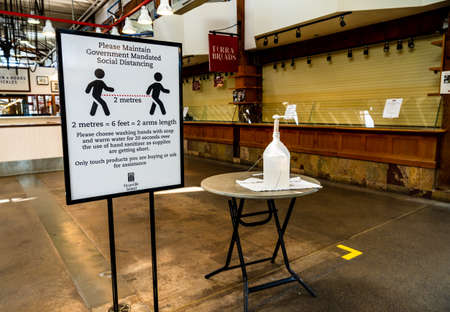 Vancouver, Canada - Apr 7, 2020: Hand sanitizer dispenser and social distancing sign in empty Granville Island Market Editöryel
