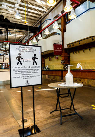 Vancouver, Canada - Apr 7, 2020: Hand sanitizer dispenser and social distancing sign in empty Granville Island Market 新聞圖片