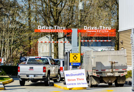 N. Vancouver - Apr 7, 2020: Cars line up before lunchtime at McDonalds for fast food during Covid-19 pandemic