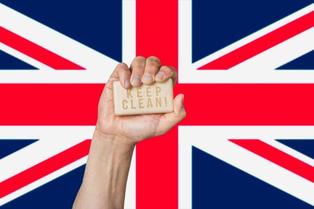 Caucasian male hand holding soap with phrase: Keep Clean, against British flag background Stok Fotoğraf
