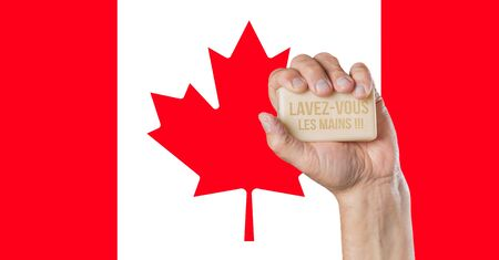Male hand holding soap with words: Lavez-vous les mains and Canadian flag behind