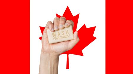 Male hand holding soap with words: Wash Your Hands, against a Canadian flag