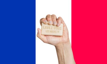 Male hand holding soap with words: Lavez-vous les mains, French flag background