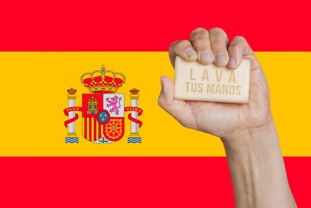 Male hand holding bar of soap with words: Lava tus manos, with Spanish flag