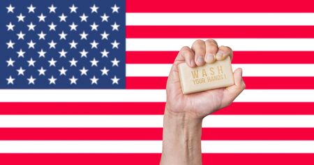 Caucasian male hand holding soap with words: Wash Your Hands against an American flag background Stok Fotoğraf