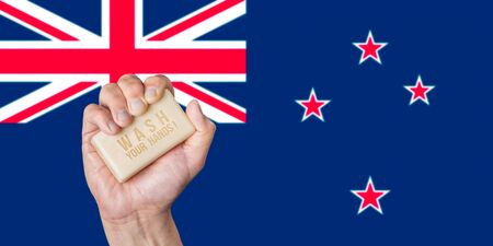 Caucasian male hand holding soap with words: Wash Your Hands against an New Zealand flag background