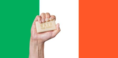 Caucasian male hand holding soap with words: Wash Your Hands against an Irish flag background Stok Fotoğraf