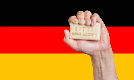 Caucasian male hand holding soap with words: Bitte Hande Waschen against a German flag background Stok Fotoğraf