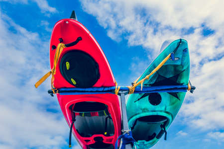 Underside of kayaks tied to rack on back of vehicle against blue sky with clouds