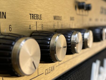 Close-up black knob, gold plate vintage combo amplifier.