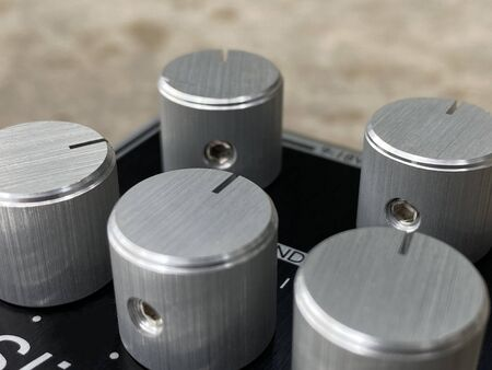 Close-up Silver metal knob and black control panel plate of boutique distortion Stomp box electric guitar effect.