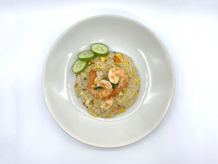 Fried rice with shrimp, big, appetizing, sprinkled with carrots, eggs, coriander and fragrant pepper, delicious, served with green cucumber on a round dish. Isolated on white background