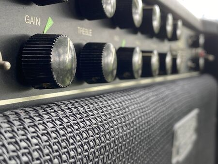 Close-up vintage head power amplifier with black knob and control panel. clean and hi-gain distortion for rock to metal, Blues, and jazz genres. Music business concept. Stock Photo
