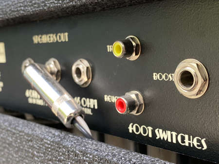 Close-up the boost input jack of a back control panel electric guitar amplifier with blurred another control panel black background. Music business concept. 免版税图像 - 151147502