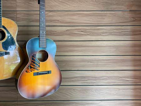 ืnatural and sunburst Two acoustic guitars hung on a brown ash wood grain wall in a music shop with copy space on the right hand for text.music or coffee shop concept. Standard-Bild
