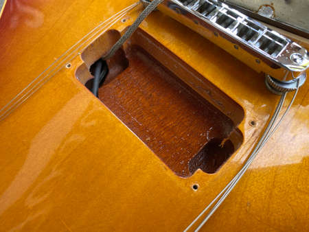 The pickup compartment of the electric guitar opens up to see the inside cherry body color can use for guitar service store or business. wallpaper and background. 免版税图像