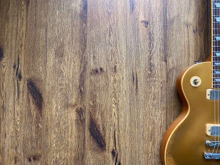 gold electric guitar made from a genuine mahogany Popular musician on veneer brown wood background with copy space on right for letter. business and music concept. Wallpaper or background. top view. Banco de Imagens