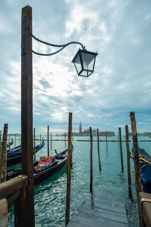 Photograph of Gondola's docked on the shore of Venice, Italy. Cloudy overcast day, surrounded by water.