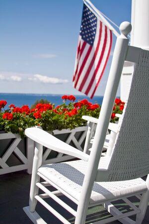 Red Geraniums, American Flag and Rocking Chair photograph. Mackinac island, Michigan. Standard-Bild