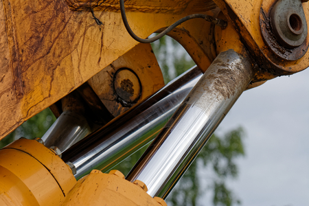 Close up of excavator hydraulic cylinders with extended piston rods