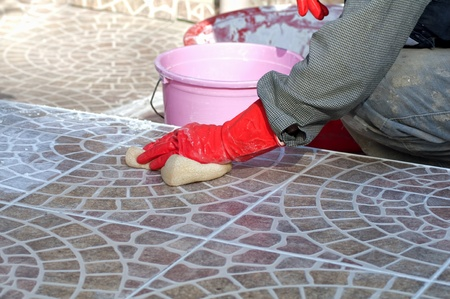 clean hand: Close up of construction worker installing decorative tiles