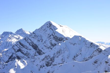 Top of the mountain in a Rose Khutor place. Snow-capped mountain peaks landscape. Blue sky background. Winter tourism nature view.