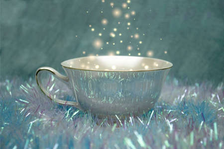 A brilliant Cup of magic drink. Christmas blue background Stock Photo