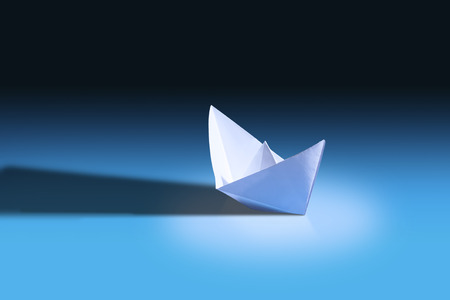 White paper boat on blue background. Origami paper ship. Stock Photo