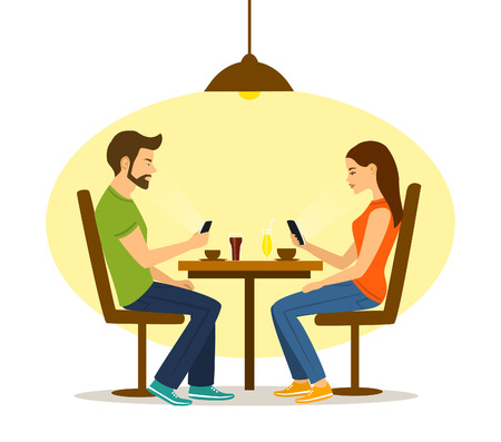 Young man and woman on a date in cafe, not talking but busy with smartphones