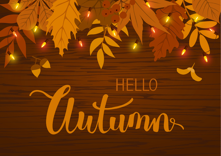 autumn fall background with leaves and  hanging festive lights bulbs garland on wooden texture